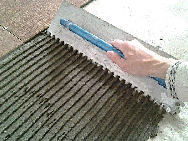 Нанесение клея на под плитку