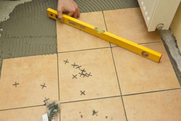 Использование строительного уровня при укладке плитки