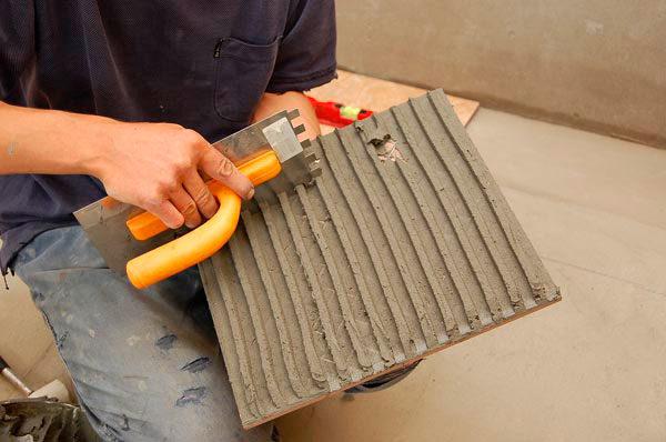 Нанесение клея на поверхность плитки