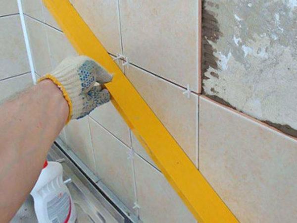 Использование строительного уровня при облицовке стен